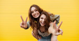 two young women who are friends smiling